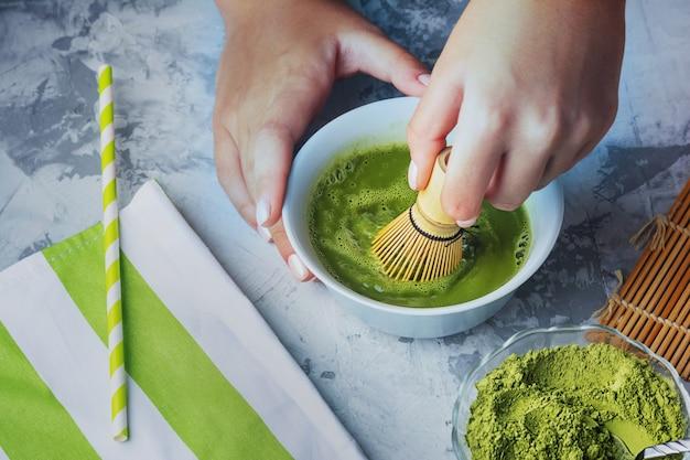 緑茶抹茶を作る工程。女性が竹泡立て器で緑の飲み物をかき混ぜる