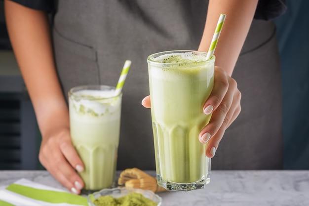クローズアップ、バリスタの手がグラスを差し出します。ストローでグラスに抹茶を飲む。便利なラテ