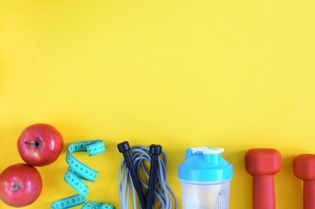 テキストのための場所とフィットネスの背景。黄色の背景にスポーツ用品。