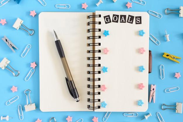 散らかった文房具とピンクの星の隣に、スプリングのメモ帳が開いています。