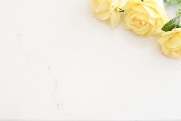 黄色いバラの明るい大理石のスタイリッシュなデスクトップ