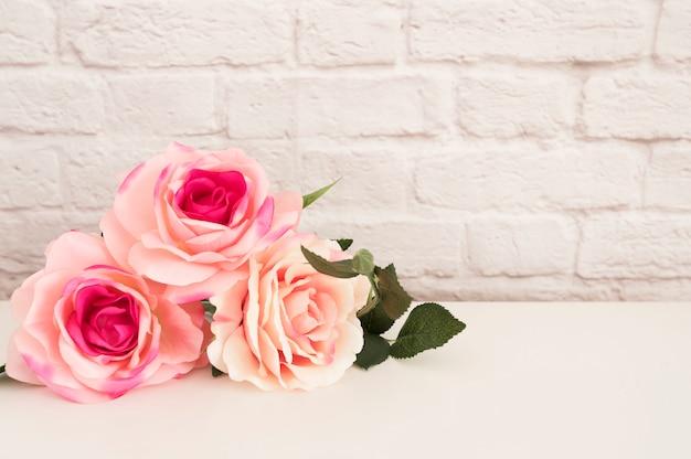白い机の上のバラの花束