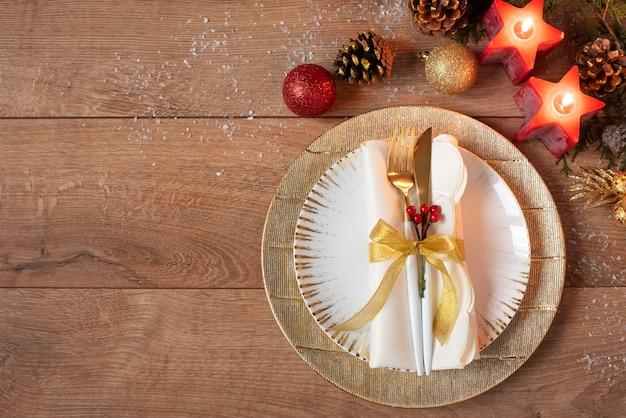 Урегулирование места рождественского ужина - тарелки, салфетка, столовые приборы, золотая безделушка на дубовом столе. вилка и ложка на золотых пластинах. вокруг красные свечи, шишки и шарики. плоская планировка