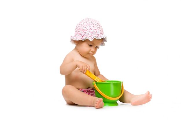 Милый маленький ребенок, играя с ведром