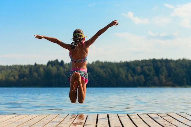 Молодая женщина прыгает в воду