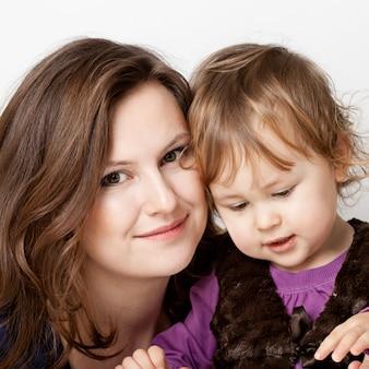 小さな女の赤ちゃんと幸せな母の肖像