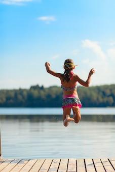 Молодая девушка прыгает в воду, летнее время
