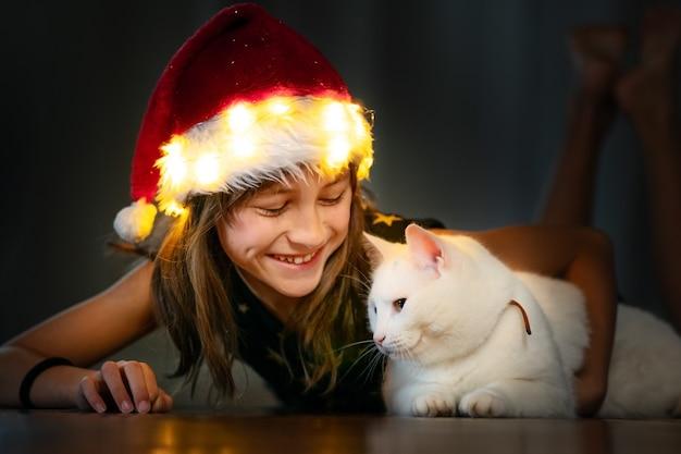 Милая маленькая девочка в шляпе рождество холдинг белый кот и улыбается.