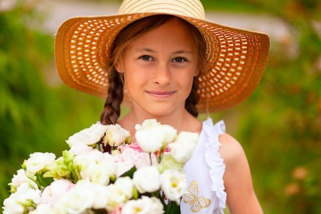白い花の花束を持つ少女。夏の日。