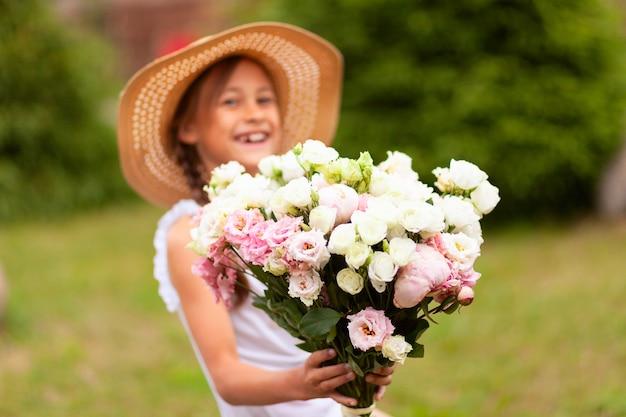 微笑んでいる女の子が手にピンクと白の牡丹の美しい花束を持っています。