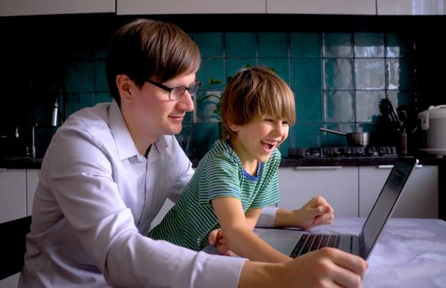 在宅勤務中、家族は自宅にいます。男は台所でノートパソコンを手にしています。