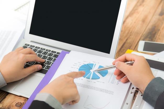 Деловые люди, сравнивающие результаты графа в офисе
