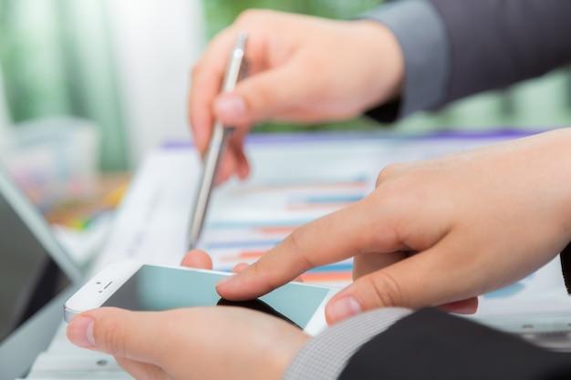 チャートとモバイル間の結果を比較するビジネス人々