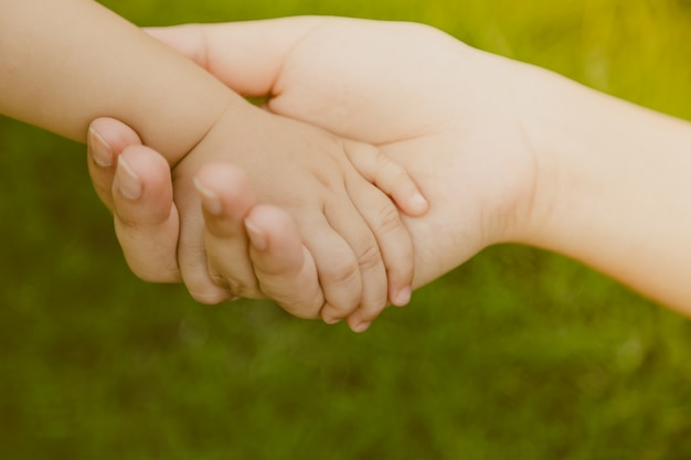 大人の手赤ちゃんの手をつかん