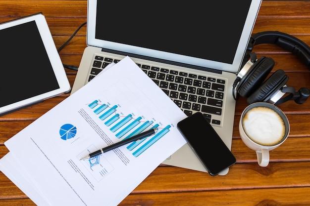 Ноутбук с бумагами с графикой на вершине