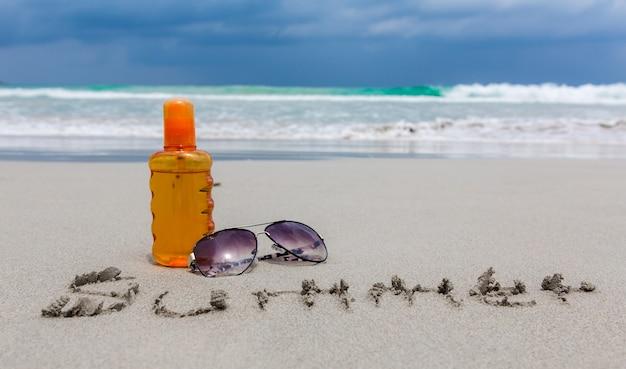 夏の時間のためのビーチで日焼け止めローションとサングラス