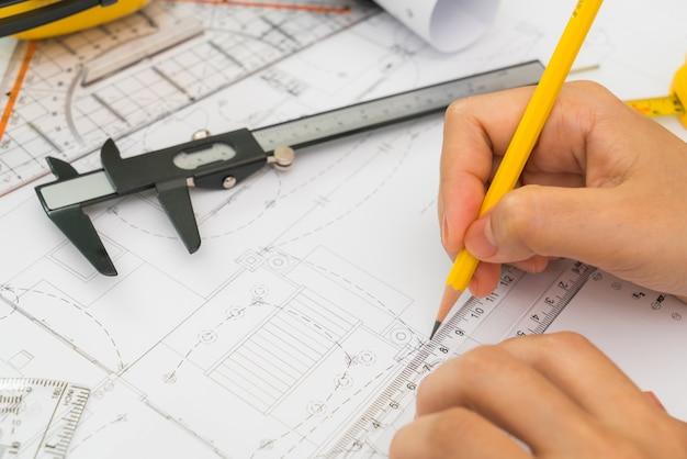 建設オーバーハンドは、黄色のヘルメットと描画ツールで計画し