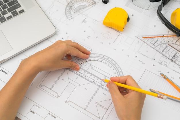 Сдайте планы строительства с желтым шлемом и инструмент для рисования
