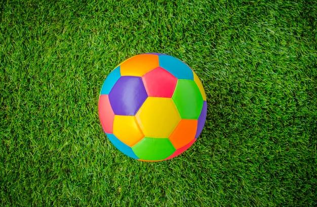 緑の芝生の上で本物の革カラフルなマルチカラーのサッカーボール。