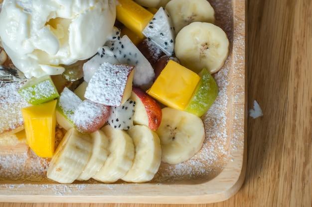 テーブルの上にアイスクリームパンケーキとフルーツ