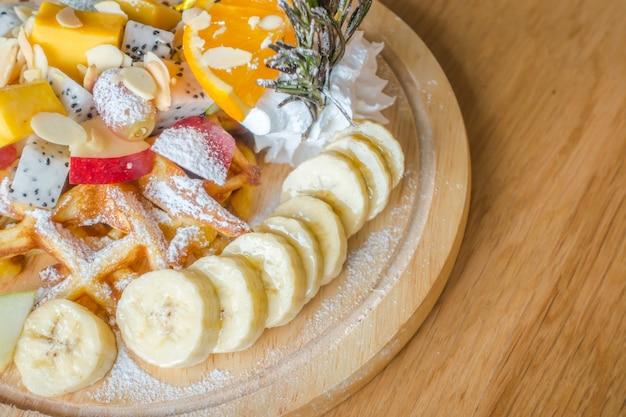 テーブルの上にアイスクリームとワッフルとフルーツ。