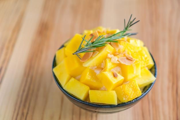 韓国スタイルの新鮮なマンゴーは木製のテーブルの上に氷を剃りました。