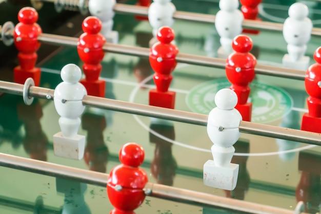 Футбол настольная игра с красным и белым игроком.