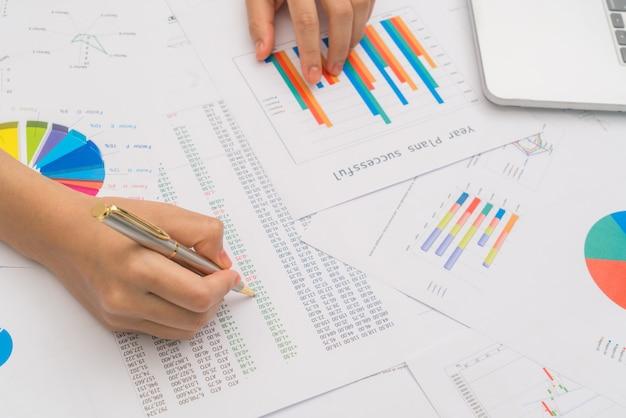 タ上の金融チャートとラップトップのビジネスの女性の手