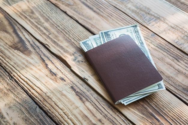 木製の板上のお金とパスポート