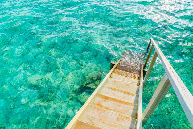 Деревянная лестница в море тропического острова мальдивы.