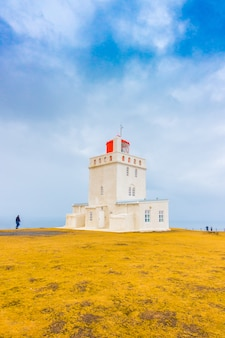 Белый маяк на мысе дырхолей, исландия. ,