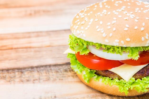 Крупный план вкусный гамбургер с сыром и салатом