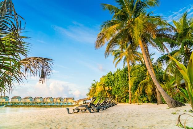 日の出時に水上ヴィラとモルディブ島のビーチチェア。