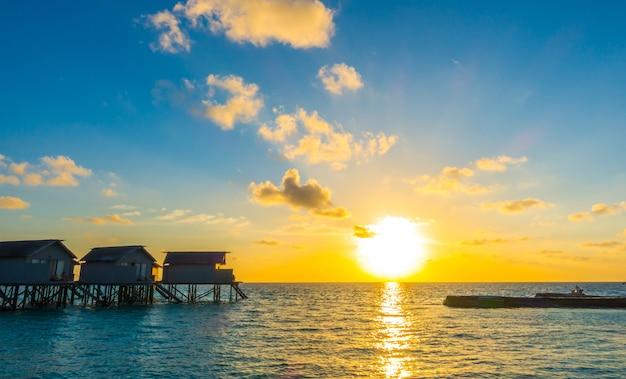 Красивый заход солнца с виллами воды в тропическом острове мальдивов.