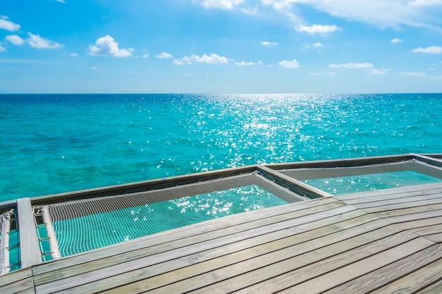 熱帯のモルディブ島の休暇ネットシートとサンゴ礁のある海の美しさ。