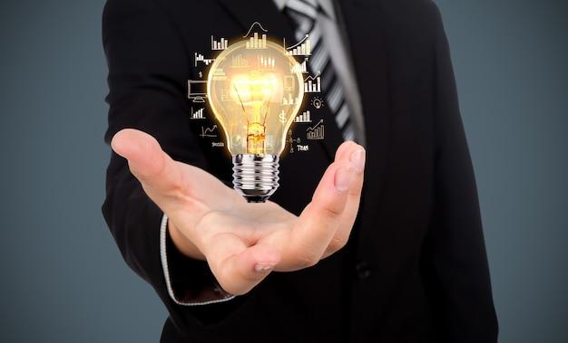 彼の手に電球を持つビジネスマン