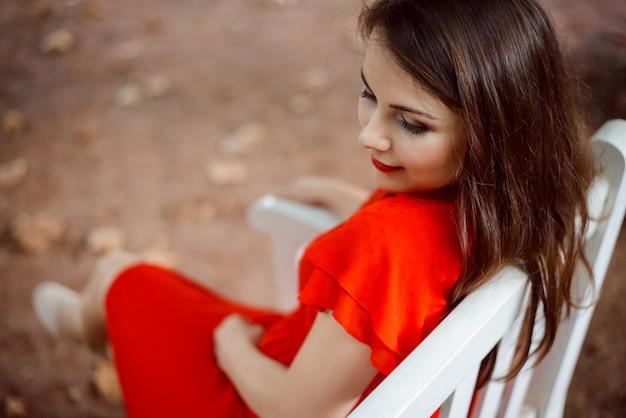 誰かを待っている公園のベンチに座っているカラフルな赤いドレスの魅力的な女の子