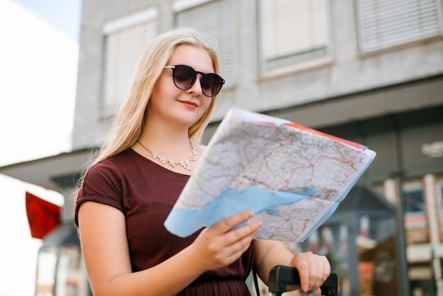 通りに立っている地図を見て若い白人の女の子