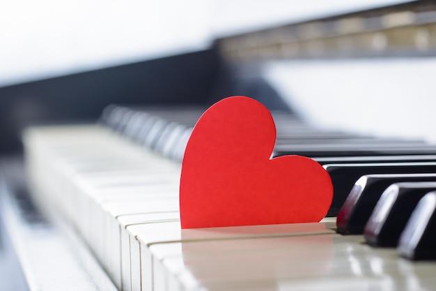 古いピアノの赤い明るいハートンキーボード。