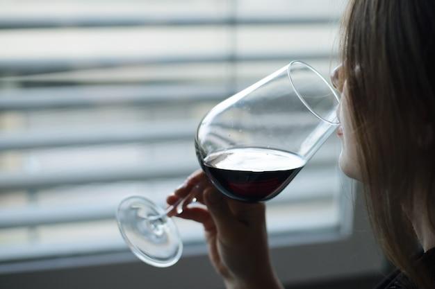 Молодая девушка с бокалом вина, глядя в окно