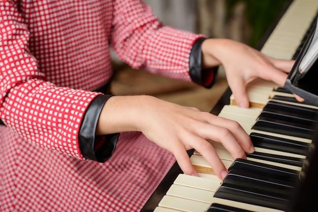 Умная маленькая девочка играет на пианино дома