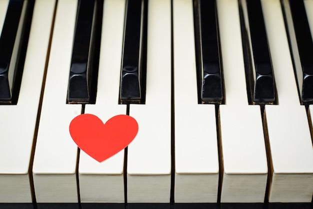 Красное сердце на клавишах клавиатуры классического старого фортепиано