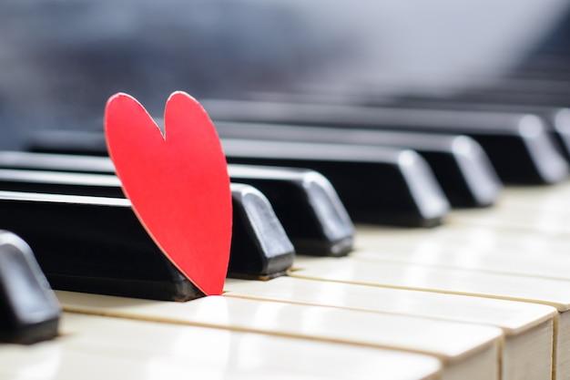 ピアノキーボードの小さな赤いハート。愛の概念、バレンタインデー