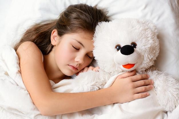眠っている間小さな美しい女の子は彼女のお気に入りのおもちゃを抱擁します。