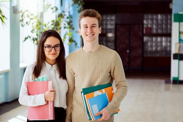 Портрет двух учеников средней школы с учебниками, учебниками и папками перед занятиями в школьном коридоре в солнечный день