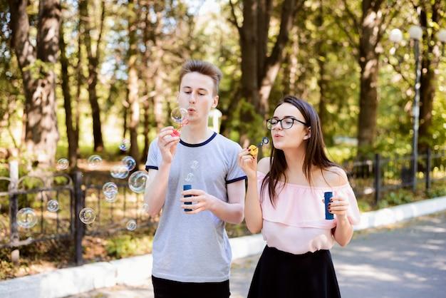 ボーイフレンドとガールフレンドは、夕方には公園でシャボン玉を吹いて、一緒に楽しんで