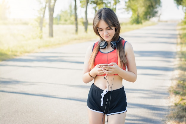 朝の田舎でのトレーニングを実行中に小さな休憩を持つ若い女の子