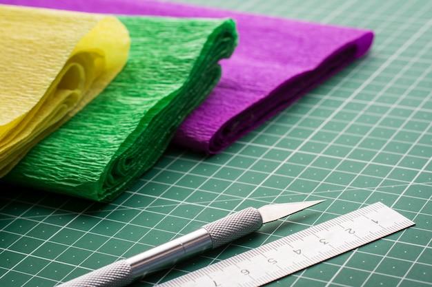 カッティングマットのアートワーク用の段ボールのロール紙の近くのメスと定規