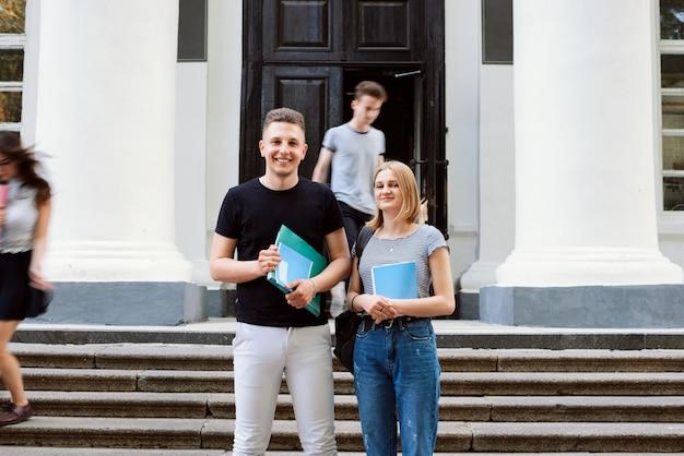 Студенты мужского и женского пола с книгами и бумагами перед занятиями у входа в здание университета с другими размытыми студентами в движении