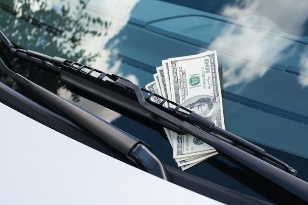 フロントガラスの車のワイパーの下の車に残った米ドル紙幣の束